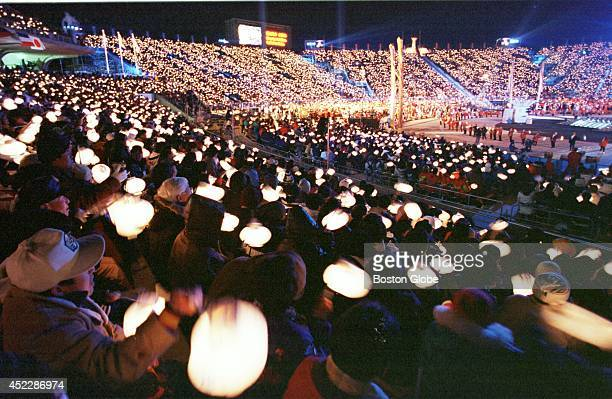 Thousands of spectators hold lit Japanese lanterns during closing ceremonies after the Olympic flame was extinguished to bring to a close the 1998...