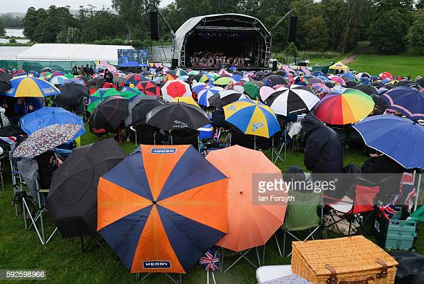 Thousands of spectators sit in the rain as they attend the annual classical Proms Spectacular concert held on the north lawn of Castle Howard on...