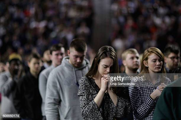 Thousands of students supporters and invited guests bow their heads in prayer before Republican presidential candidate Donald Trump delivers the...