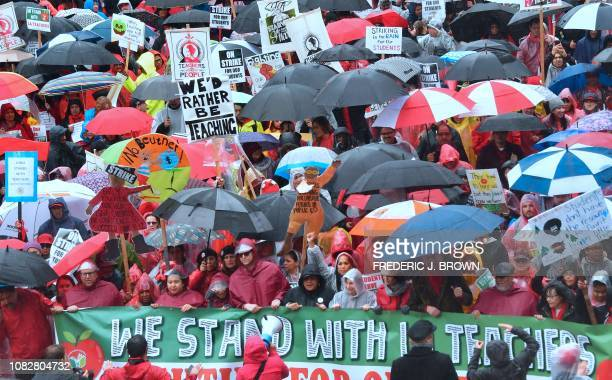 Thousands of teachers march in the rain through Los Angeles California on January 14 on the first day of the first teachers strike in 30 years...