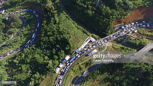 Thousands of travellers heading to their hometowns to celebrate Eid alFitr wait in a massive traffic jam on July 8 2016 in Tasikmalaya West Java...