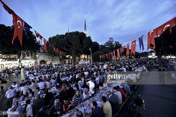Thousands of Turkish people break their fasting on June 18 2015 at the Blue Mosque square in Istanbul during the first day of the holy month of...