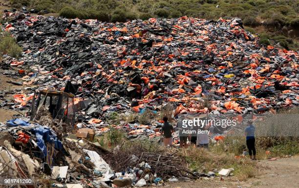 Thousands of used life preservers and pieces of rafts used by refugees in their attempted crossings from Turkey to Greece lay in a pile on the island...