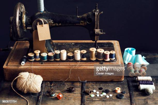 thread reels on sewing machine at table - ribbon sewing item stock pictures, royalty-free photos & images