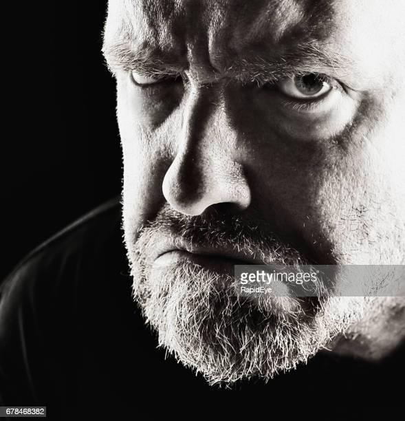 Bedrohlich, wütend reifer Mann Glowers in schwarz und weiß
