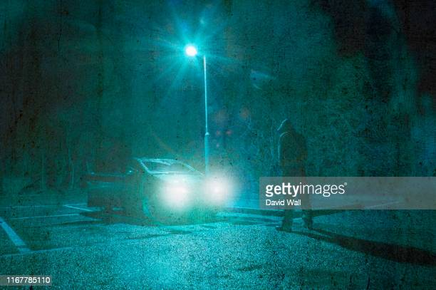 a threatening lone hooded figure standing next to a car underneath a street light at night. highlighted with car headlights. with deliberate lens flare. and vintage, grunge edit. - hooded top stock pictures, royalty-free photos & images