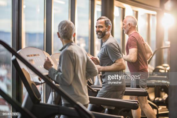 three active seniors exercising on treadmills in a health club and communicating. - treadmill stock pictures, royalty-free photos & images
