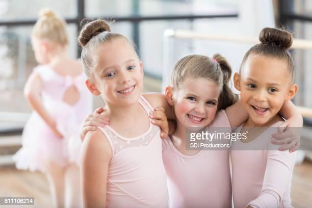 Three adorable young ballerinas smile arm in arm