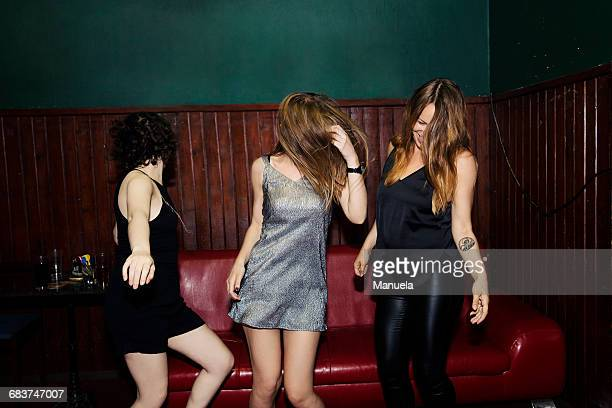 Three adult female friends dancing in club on night