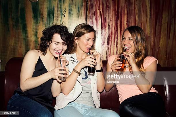 Three adult female friends drinking in bar