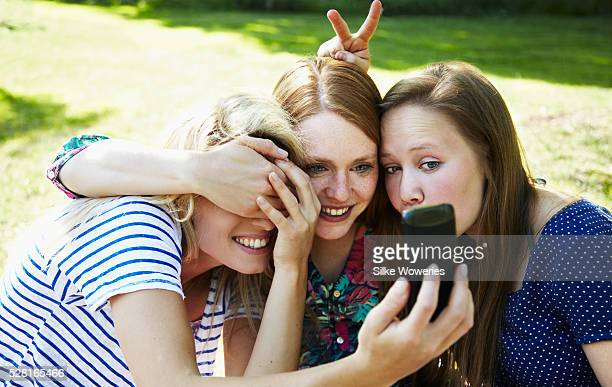 three adult female friends hanging out in a park and having fun taking a selfie