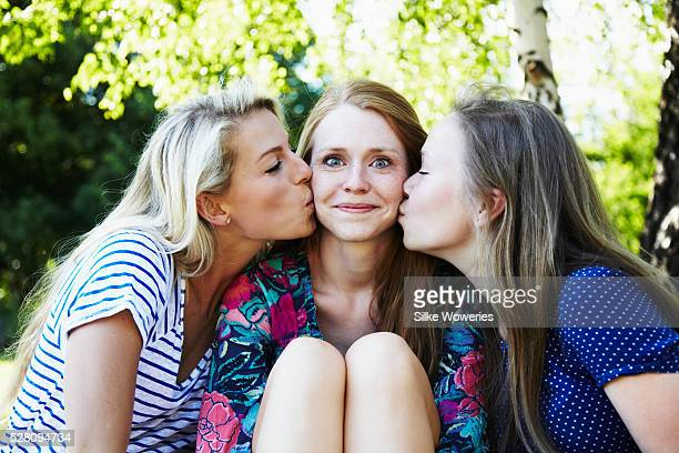 three adult female friends hanging out in a park and having fun