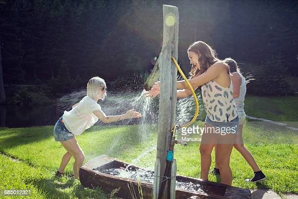 three adult female friends play fighting sprinkling water hose in garden - women in wet t shirts stock pictures, royalty-free photos & images