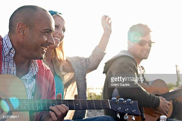 Three adult friends playing acoustic guitars on Bournemouth beach, Dorset, UK