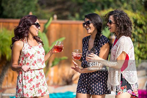 Three adult sisters gossiping and drinking rose wine in garden