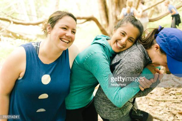 three adult sisters hugging and laughing in forest, maine, usa - heshphoto stock pictures, royalty-free photos & images