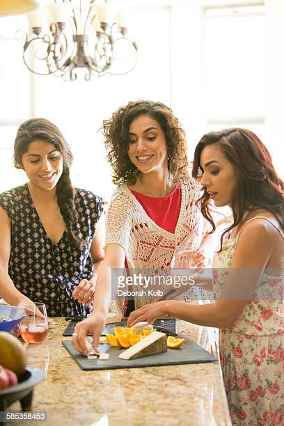 Three adult sisters snacking from cheese board