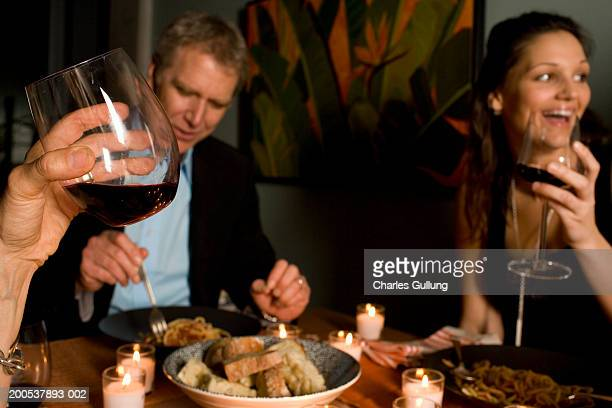Three adults eating and drinking red wine at dining table