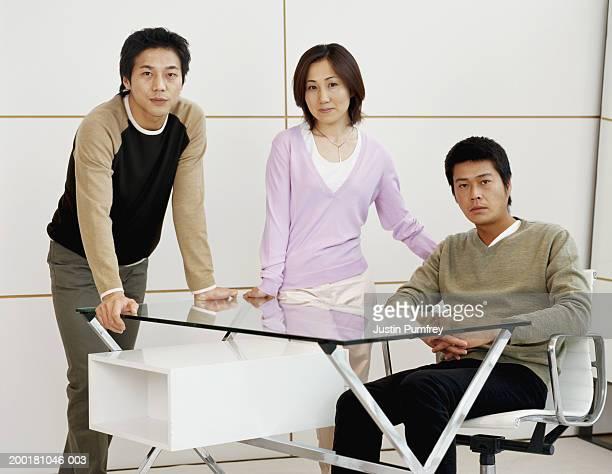 three adults in office by desk, portrait - ビジネスウェア ストックフォトと画像