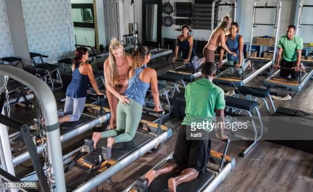 tre adulti nello studio di pilates con istruttore di fitness - solo adulti foto e immagini stock