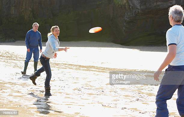 Three adults playing Frisbee on the beach