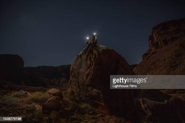 Three adventurous friends sit atop a large boulder at night and gaze out at landscape and stars while wearing lit headlamps in Moab, Utah.