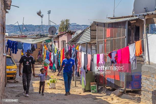 three african people in an alley in alexandra township, johannesburg - alexandra township stock pictures, royalty-free photos & images