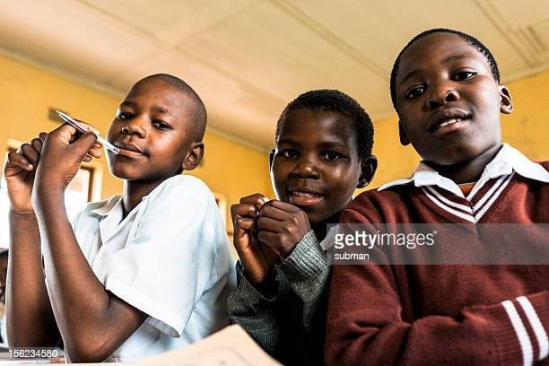 Three African students in a yellow classroom