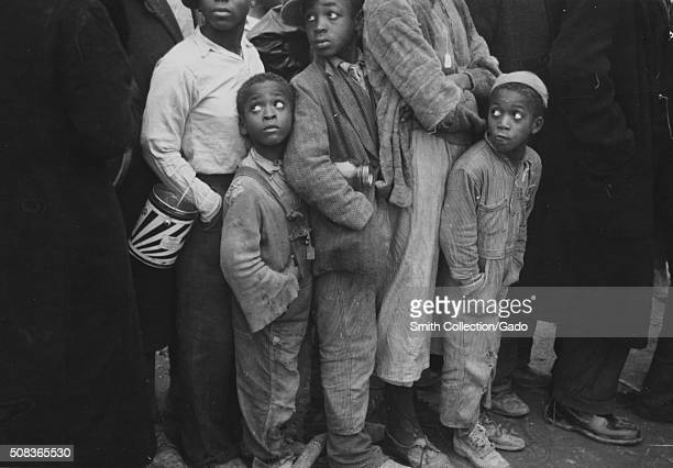 Three AfricanAmerican children standing in line with other flood refugees children and adults for mealtime Forrest City Arkansas 1937 From the New...
