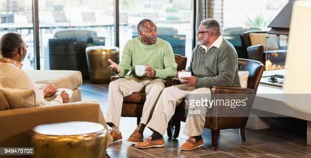 コーヒーを飲みながら話している 3 つのアフリカ系アメリカ人