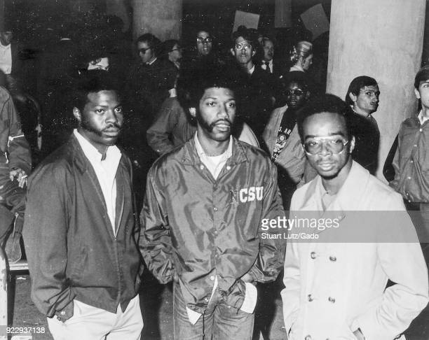 Three AfricanAmerican students with afro haircuts stand among a crowd during an anti Vietnam War student sitin protest at North Carolina State...