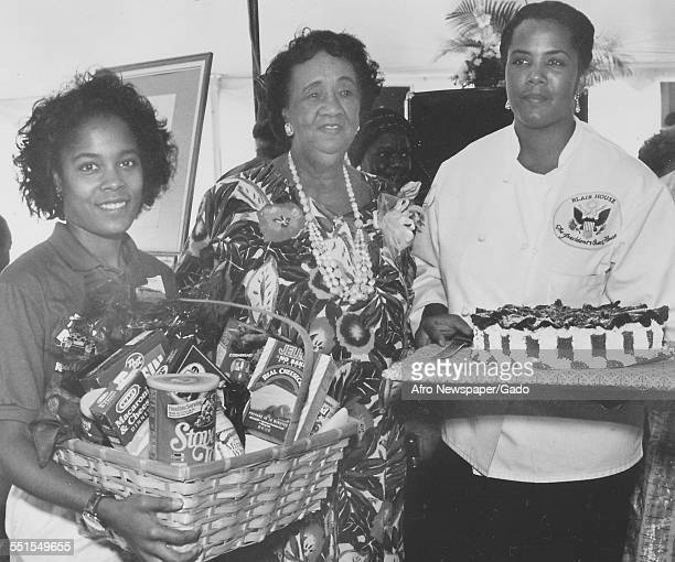 Three AfricanAmerican women carrying presents or prizes a fruit basket and a large cake for a celebration 1992