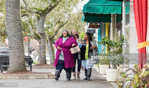 três mulheres afro-americanas que andam na cidade - amizade feminina - fotografias e filmes do acervo