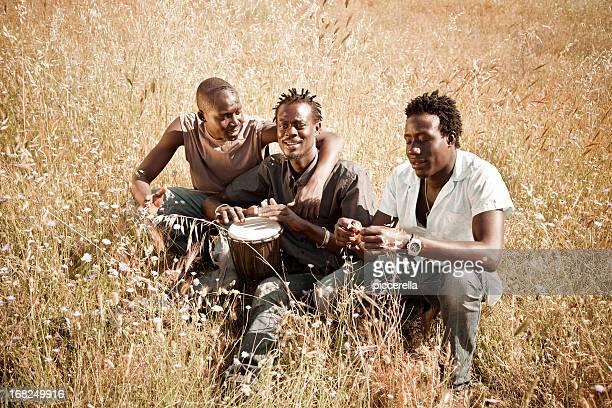 Trois africains hommes jouant Djembé dans la Prairie