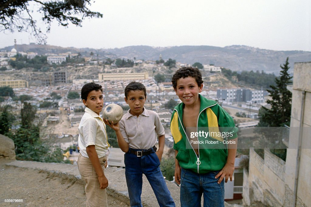 Three Algerian boys play with a ball on a hill overlooking Algiers.