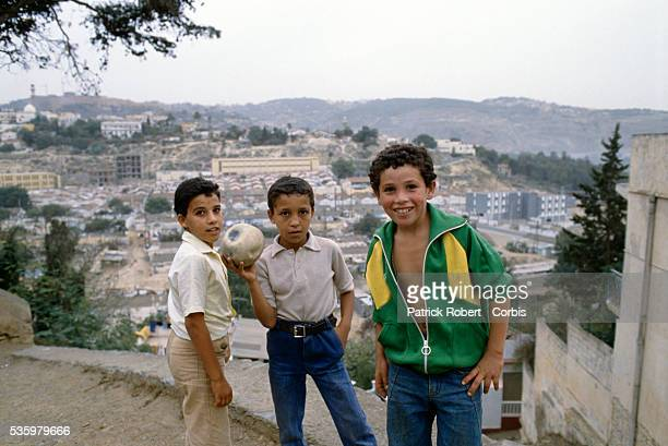 Three Algerian boys play with a ball on a hill overlooking Algiers