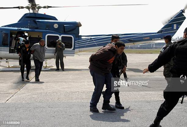 Three alleged members of Mexican drug cartel Los Zetas are escorted by members of the National Civil Police upon arrival at the Guatemalan Air Force...