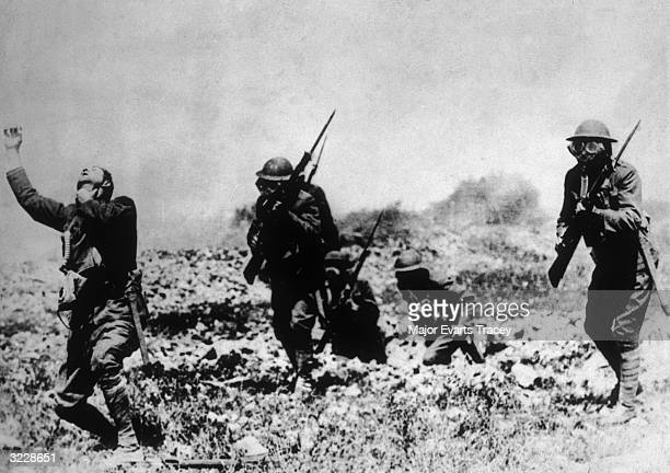 Three Allied soldiers wearing gas masks and running through a poison gas cloud in a staged battle photograph France World War I