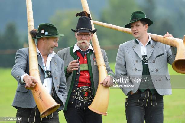 Three Alphorn blowers walk down a hill with their instruments after their performance at the Alphorn blowers meeting in WeilerSimmerberg Germany 25...