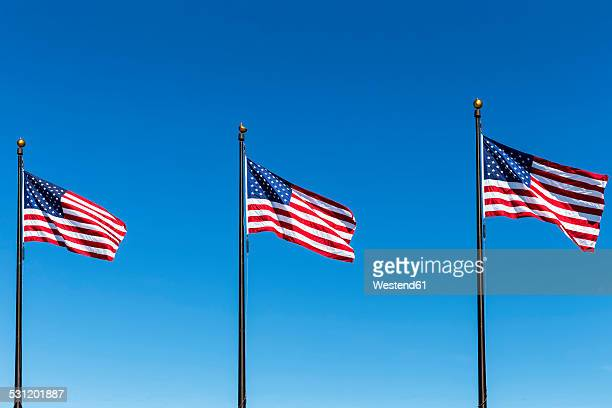 Three American flags against blue sky