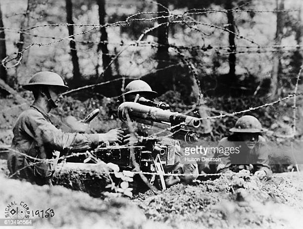 Three American soldiers operate a French '37' one pounder gun set in firing position in a second line trench at the Western Front, World War I.  ...