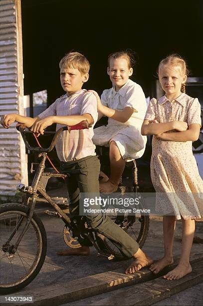 Three Amish children on a bicycle Belize