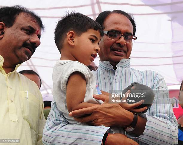 Three and half year old Prateek Soni handing over his piggy bank to chief minister Shivraj Singh Chouhan for Nepal earthquake victims relief fund, on...