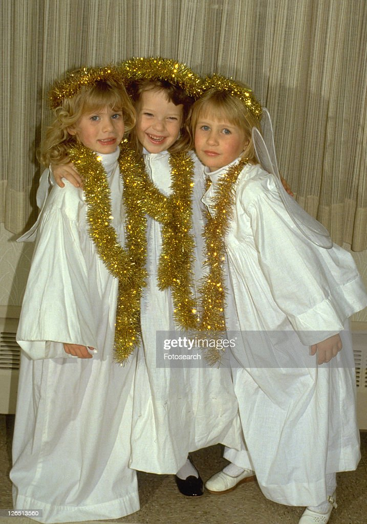 Three angels age 8 smiling at Christmas pageant : Stock Photo