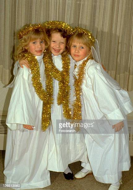 three angels age 8 smiling at christmas pageant - nativity stock photos and pictures