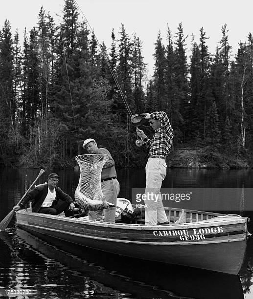 Three anglers land a northern pike in a net while fishing near the Caribou Lodge in Canada circa 1960