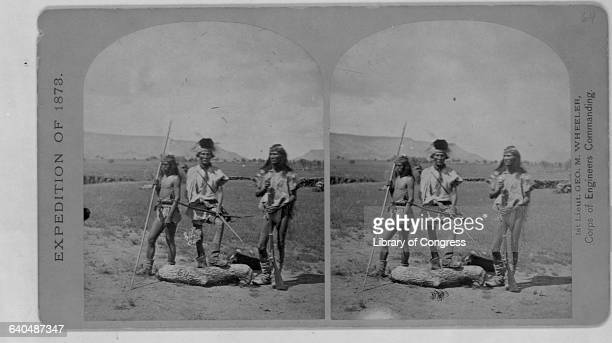 Three Apache Indians appear ready for war One has a spear another holds a bow and arrow and the third is equipped with a rifle