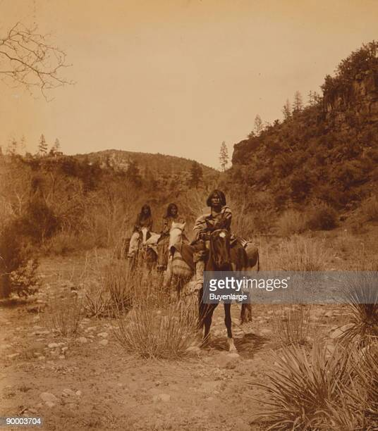 Three Apache people riding pack horses make their way along rocky bottom land