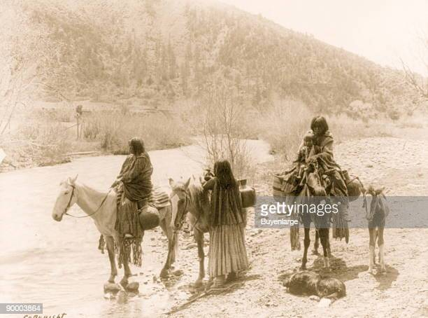 Three Apaches one with a child with horses laden with water jugs a colt and a dog stopped beside a stream