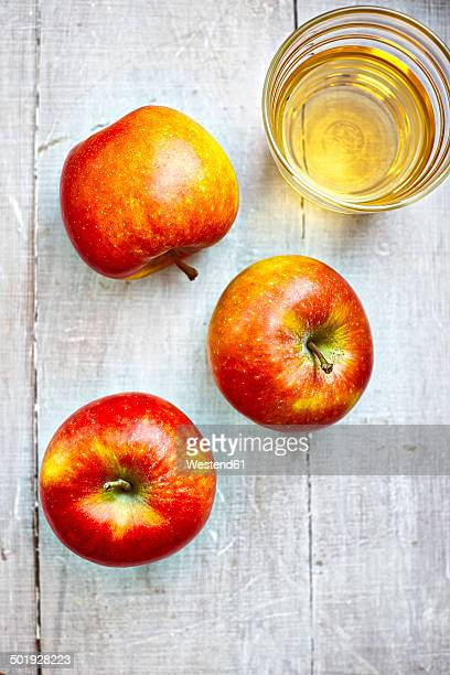 Three apples and a glass of apple juice on grey wood, elevated view